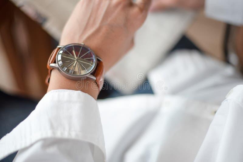 Chronométrez la conservation pour le rendez-vous important, regards d'un homme sur le sien montre photos libres de droits