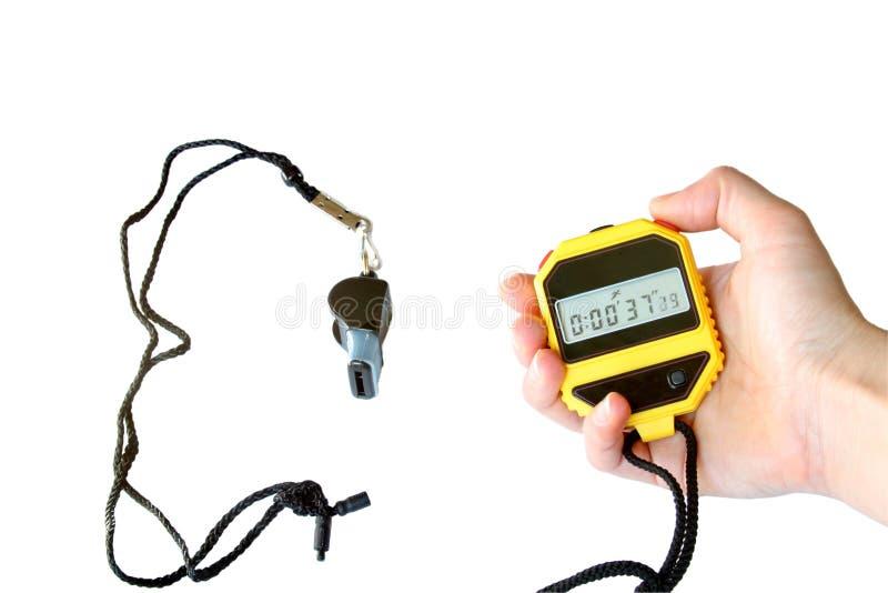 Chronometer in de hand en het sportenfluitje stock foto's