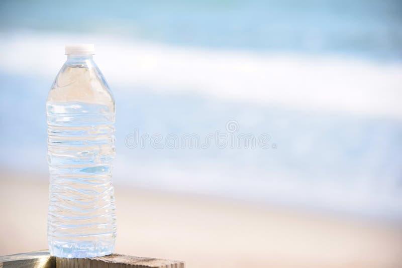 Chrupiąca butelka woda przy plażą obraz stock