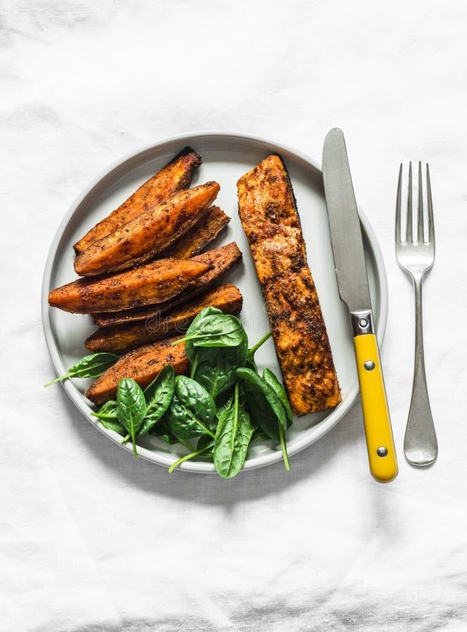 Chrupiąca skórka z przypraw pieczona łosoś ze słodkim ziemniakiem i szpinakiem - zdrowy, zrównoważony obiad na jasnym tle, widok  obraz stock