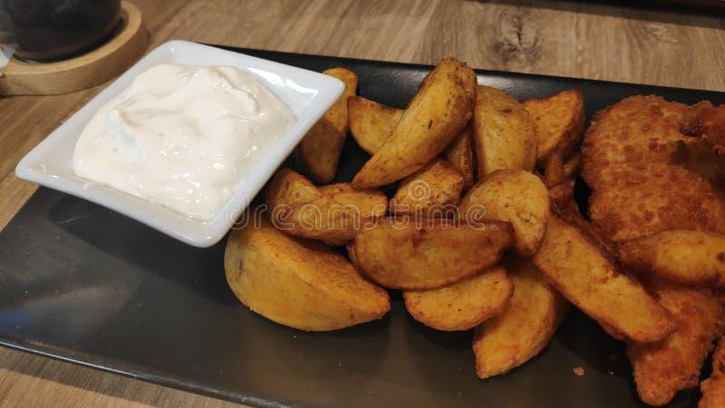 Chrupiące paski z piersi kurczaka ze złotymi ziemniakami i sosem tzatziki serwowane na czarnej prostokątnej płytce zdjęcie stock