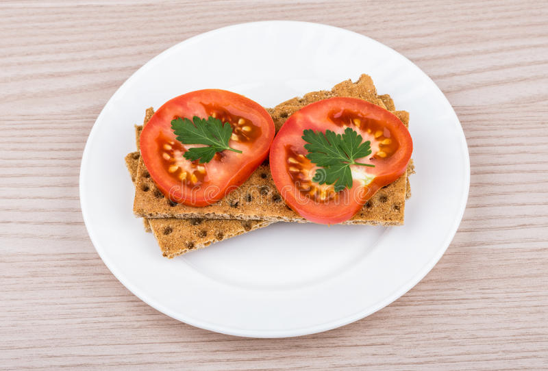 Chrupiący chleb z plasterkiem pomidory w talerzu na stole obrazy royalty free