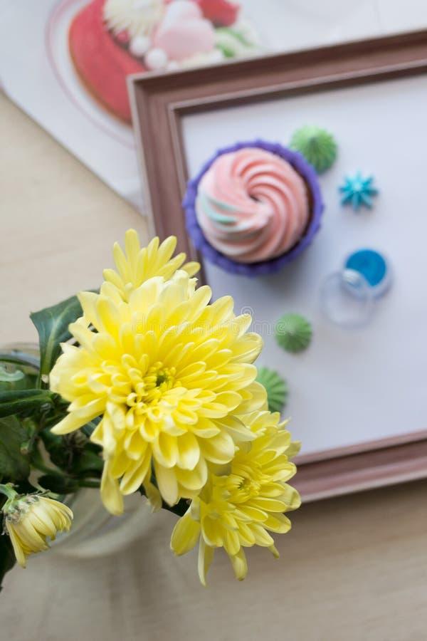 Chrysanthème jaune au foyer sur le fond du cadre en bois avec les petits gâteaux et la meringue, flatlay image stock