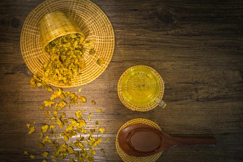 Chrysanthemum tea and honey bee on wood background. Extend the arteries at the heart. Help prevent artery diseases such as hypertension, angina.It absorbs stock photo
