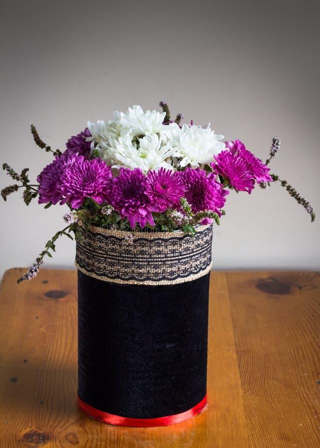 Chrysanthenums dans un velours noir rustique a couvert le vase d'embroi photographie stock libre de droits
