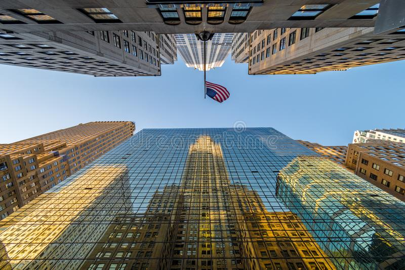 Chrysler building in glass windows reflection with american flag above at sunset, New York city, USA royalty free stock photo
