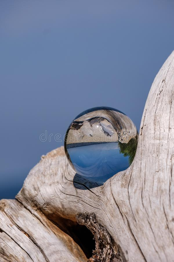 Chrystal ball on a dry wood on the beach. In summer, reflections of the sea and sky royalty free stock photography