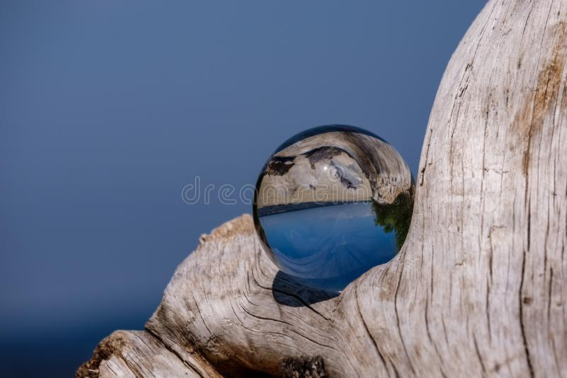 Chrystal ball on a dry wood on the beach. In summer, reflections of the sea and sky stock image