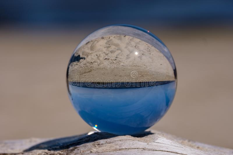 Chrystal ball on a dry wood on the beach. In summer, reflections of the sea and sky stock photography