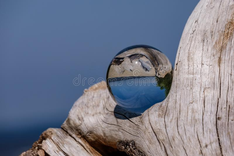 Chrystal ball on a dry wood on the beach. In summer, reflections of the sea and sky stock images