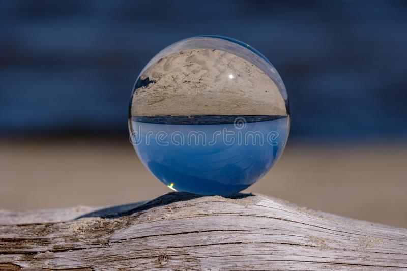 Chrystal ball on a dry wood on the beach. In summer, reflections of the sea and sky royalty free stock photos