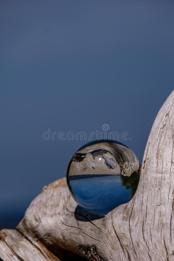 Chrystal ball on a dry wood on the beach. In summer, reflections of the sea and sky stock photo