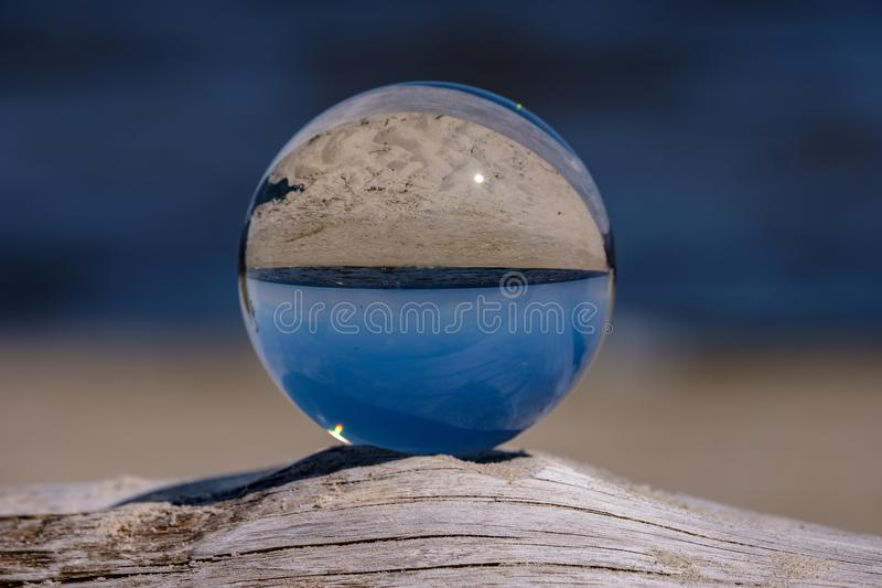 Chrystal ball on a dry wood on the beach. In summer, reflections of the sea and sky royalty free stock image