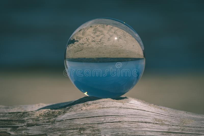 Chrystal ball on a dry wood on the beach - vintage retro look. Chrystal ball on a dry wood on the beach in summer, reflections of the sea and sky - vintage retro royalty free stock photo