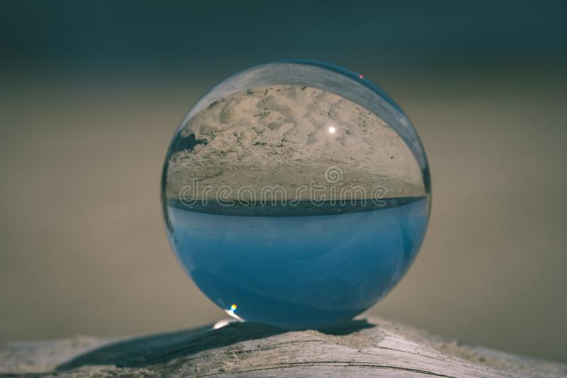 Chrystal ball on a dry wood on the beach - vintage retro look. Chrystal ball on a dry wood on the beach in summer, reflections of the sea and sky - vintage retro stock photos