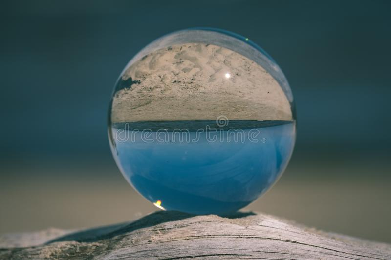 Chrystal ball on a dry wood on the beach - vintage retro look. Chrystal ball on a dry wood on the beach in summer, reflections of the sea and sky - vintage retro stock photography