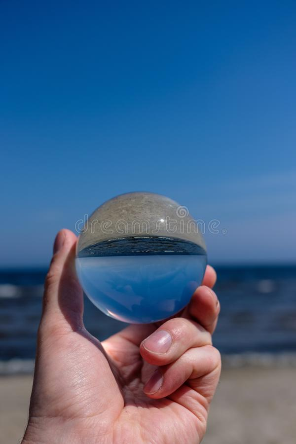 Chrystal ball on a mans palm on the beach. In summer, reflections of the sea and sky stock photo