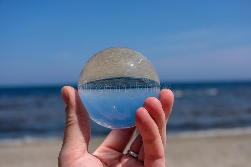 Chrystal ball on a mans palm on the beach. In summer, reflections of the sea and sky royalty free stock image