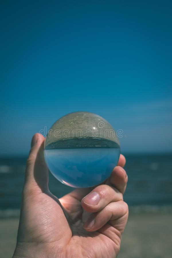 Chrystal ball on a mans palm on the beach - vintage retro look. Chrystal ball on a mans palm on the beach in summer, reflections of the sea and sky - vintage stock photos