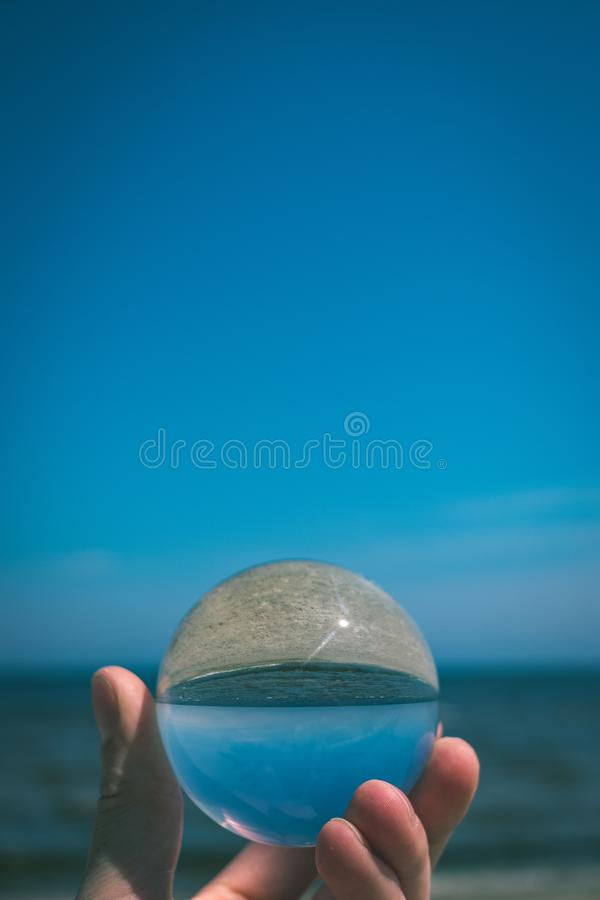 Chrystal ball on a mans palm on the beach - vintage retro look. Chrystal ball on a mans palm on the beach in summer, reflections of the sea and sky - vintage royalty free stock images