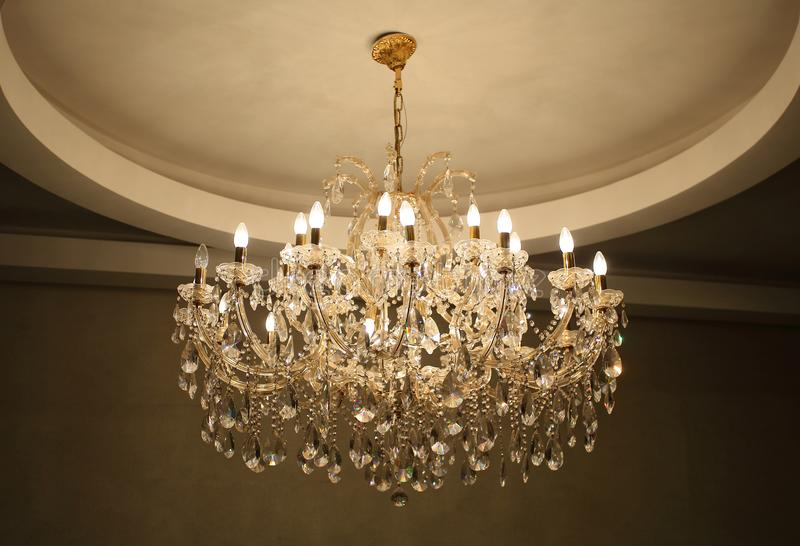 A Chrystal chandelier hang from ceiling.  stock photography