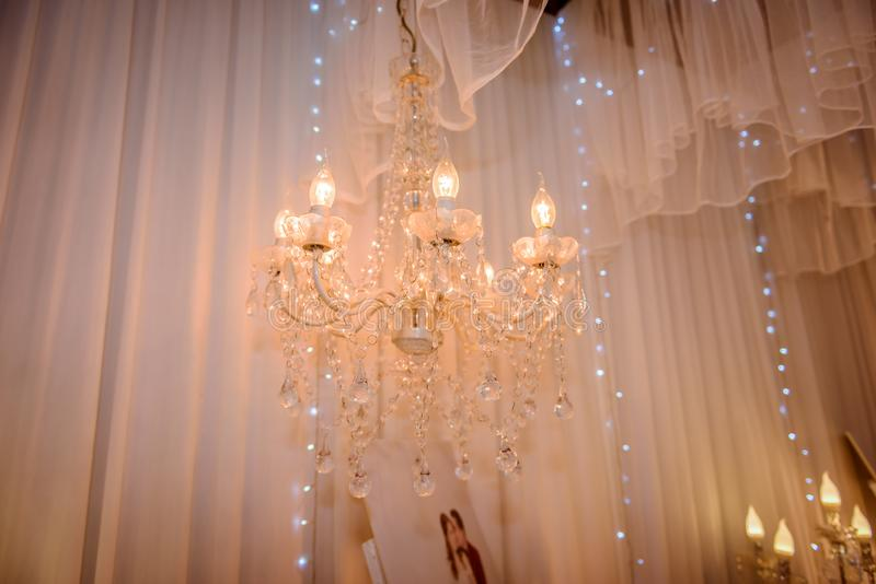 Chrystal chandelier lamp with white curtain. Decorative elegant vintage and Contemporary interior or wedding ceremony Concept stock photo