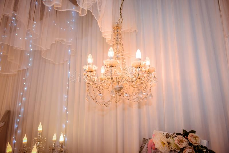 Chrystal chandelier lamp with white curtain. Decorative elegant vintage and Contemporary interior or wedding ceremony Concept stock photos