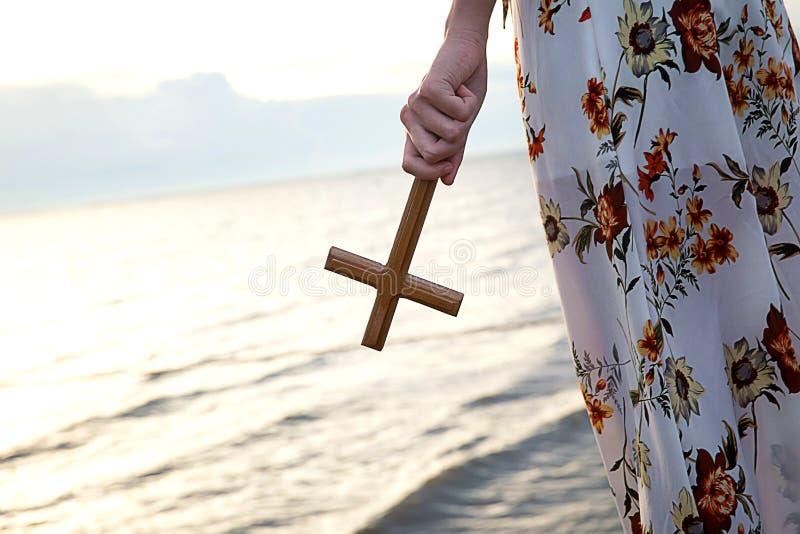 Chrześcijańska damy dziewczyna trzyma świętego krzyż w jej ręce i pozycję na plaży podczas zmierzchu wieczór czasu zdjęcia stock