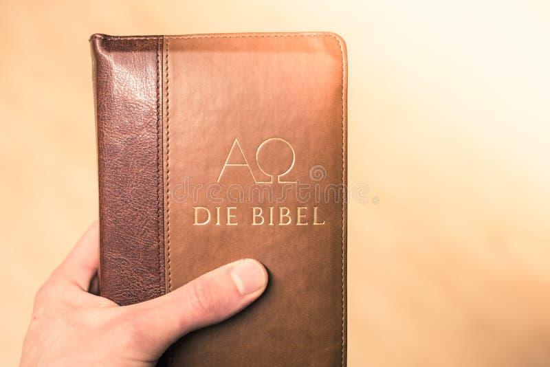 Chrze?cija?ska kaznodzieja: M?ody cz?owiek trzyma bibli?, ono modli si? fotografia royalty free