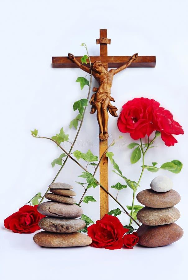 Chrześcijański krzyż z czerwonymi różami, bluszczem i kamieniem, góruje zdjęcia royalty free