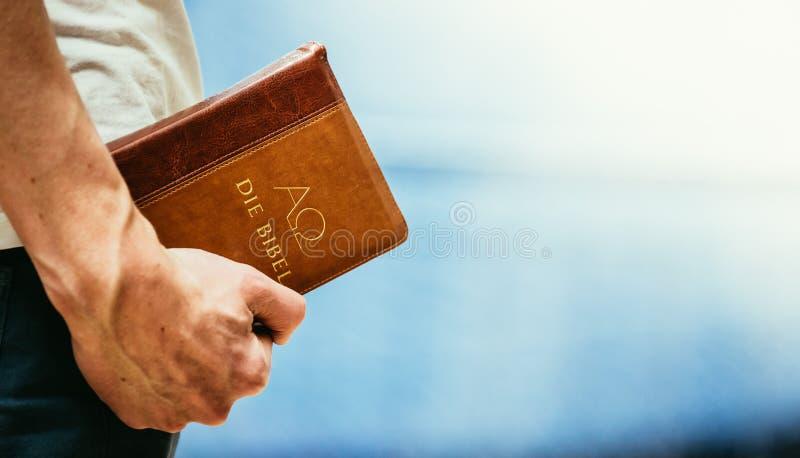 Chrze?cija?ska kaznodzieja: M?ody cz?owiek trzyma bibli?, ono modli si? obraz royalty free
