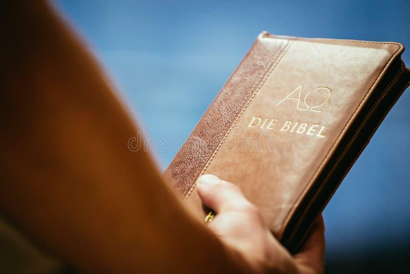 Chrze?cija?ska kaznodzieja: M?ody cz?owiek trzyma bibli?, ono modli si? zdjęcie stock