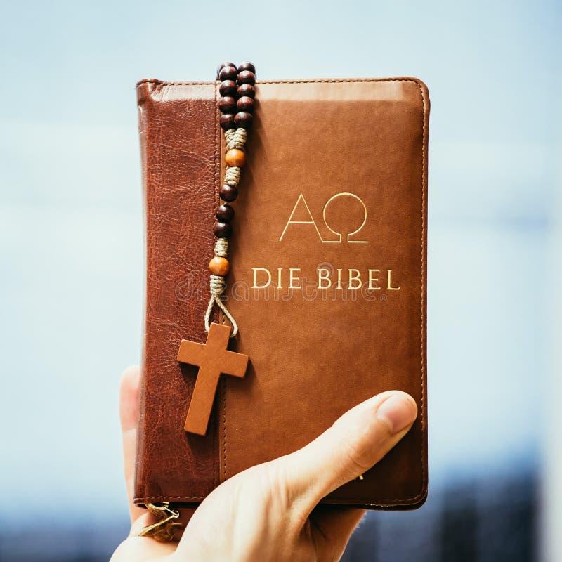 Chrze?cija?ska kaznodzieja: M?ody cz?owiek trzyma bibli?, ono modli si? zdjęcie royalty free