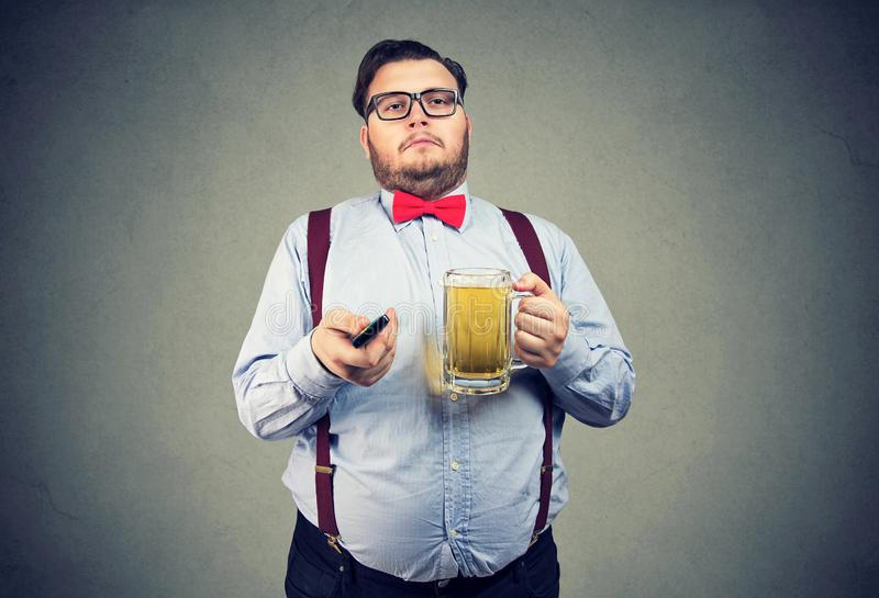 Chubby άτομο με την μπύρα και TV μακρινή στοκ εικόνες