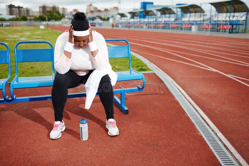 Chubby γυναίκα που ανακτεί μετά από το σκληρό workout στο στάδιο στίβου στοκ φωτογραφίες με δικαίωμα ελεύθερης χρήσης