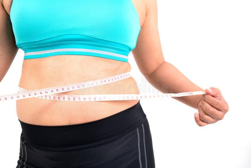 Chubby γυναίκα που μετρά το waistline της στοκ φωτογραφία με δικαίωμα ελεύθερης χρήσης