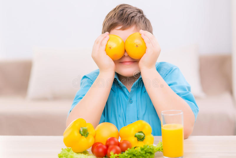 Chubby παιχνίδι παιδιών με τα πορτοκάλια στοκ φωτογραφία με δικαίωμα ελεύθερης χρήσης