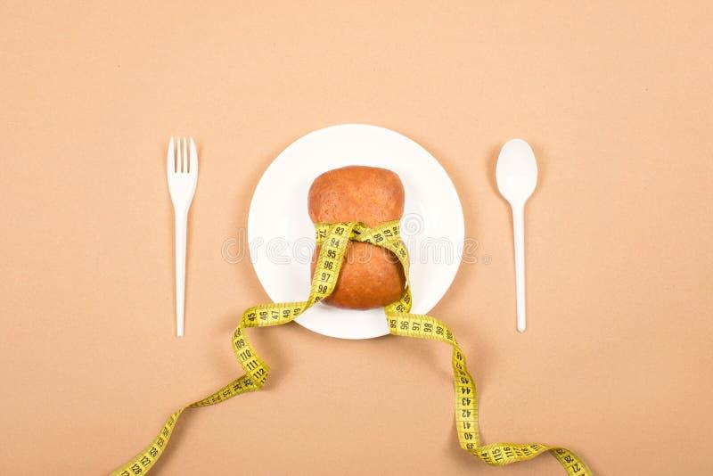 Chubby Bun met een taille haalde door band op witte plaat met lepel, vork te meten aan Het dieet, weegt verlies, het gezonde eten royalty-vrije stock fotografie