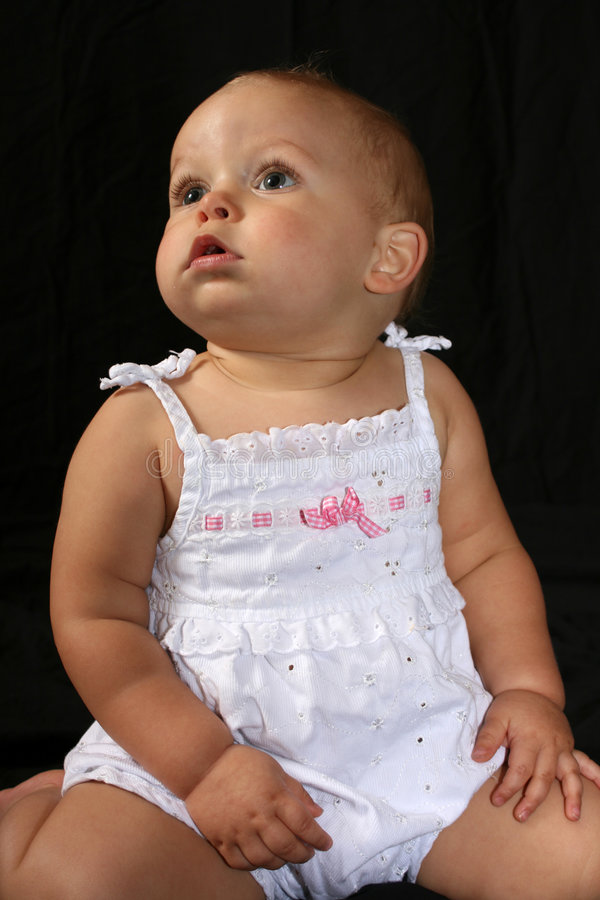 Chubby Cheeks. Photo of a beautiful baby girl with chubby cheeks looking off into the distance royalty free stock photos