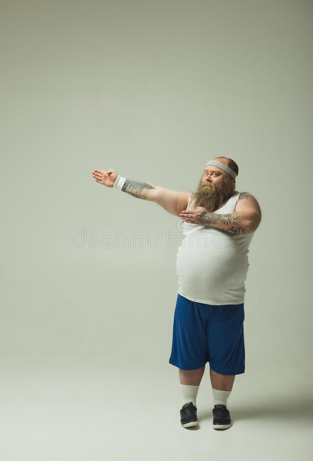 Chubby guy in sportswear showing the way by arms royalty free stock image