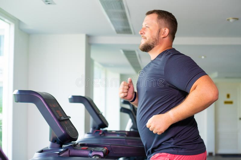 Chubby man walking on running track, warming up on gym treadmill. stock photography