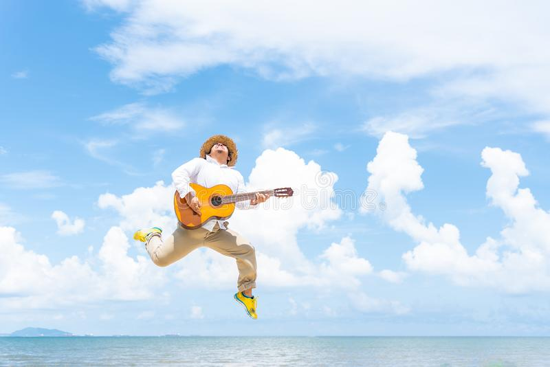 Chubby man wearing hat jumping while playing guitar stock photography