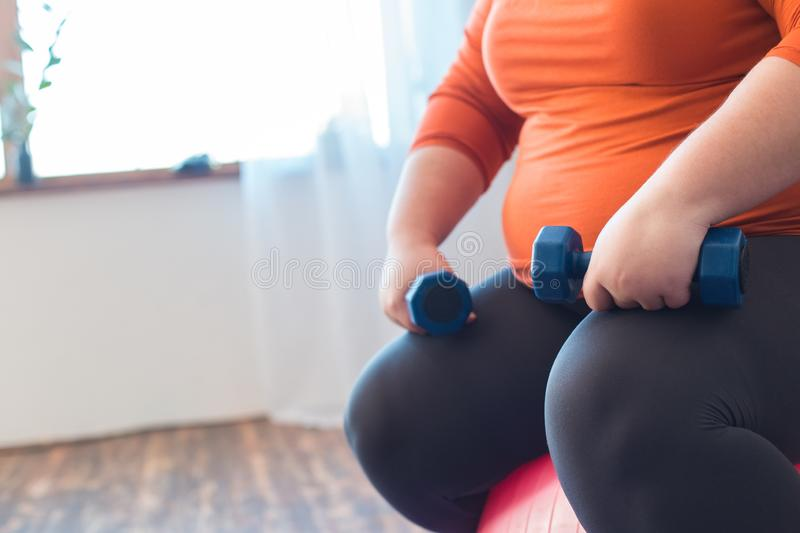Chubby woman sport at home sitting on ball with dumbbells close-up royalty free stock photography