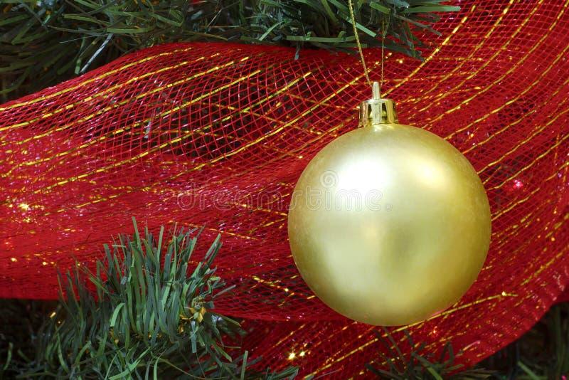 Chuchería grande de la Navidad del oro en una cinta del rojo del árbol foto de archivo