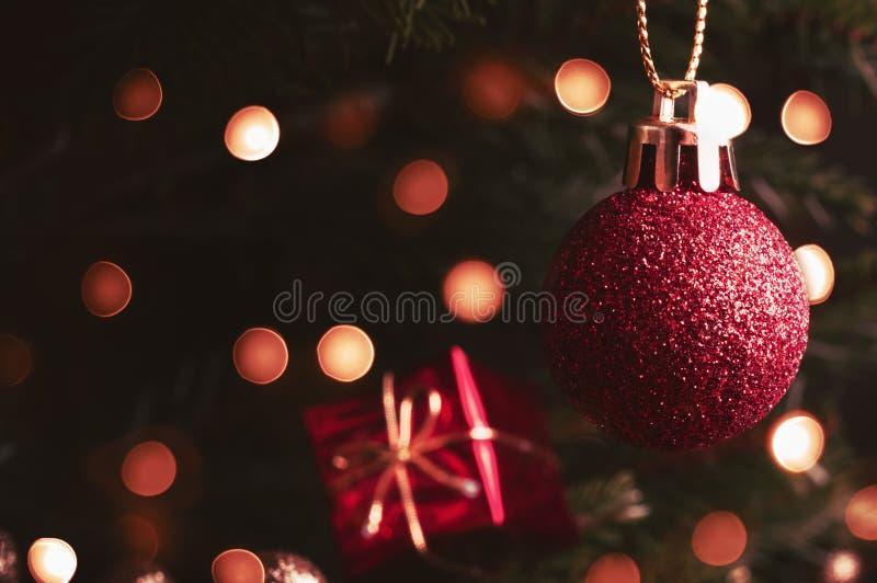 Chuchería y regalo de la Navidad en árbol con las luces de Bokeh en pocilga retra imagen de archivo