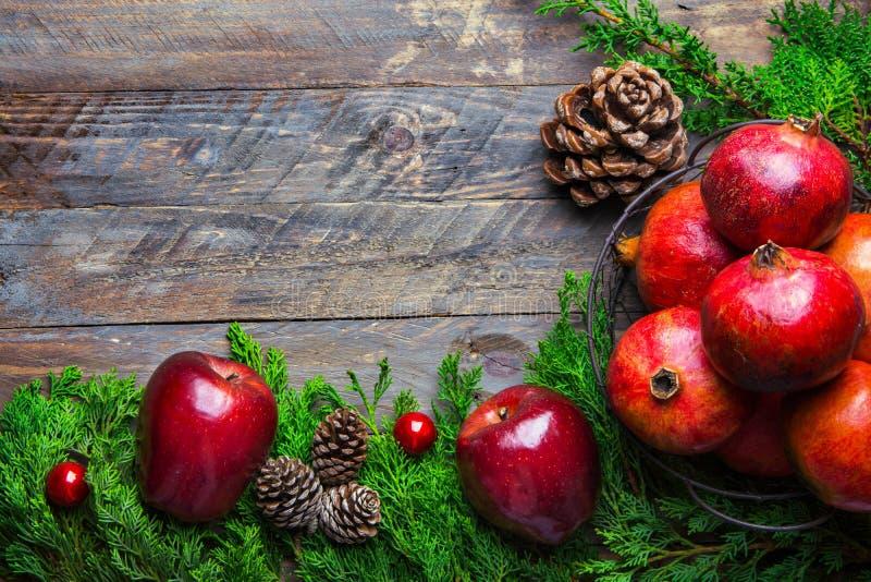 Chucherías rojas de los conos del pino de las granadas de las manzanas del enebro verde fresco de la bandera de la tarjeta del ca foto de archivo libre de regalías