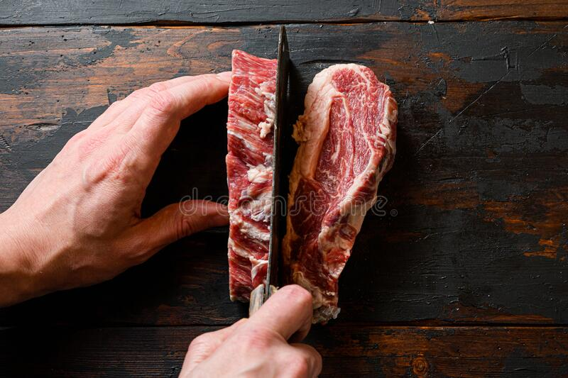 Chuck eye roll steak with butcher hands man cut meat with meat cleaver. Organic beef. at work chop. over dark wooden plank. Background Space for text royalty free stock photo