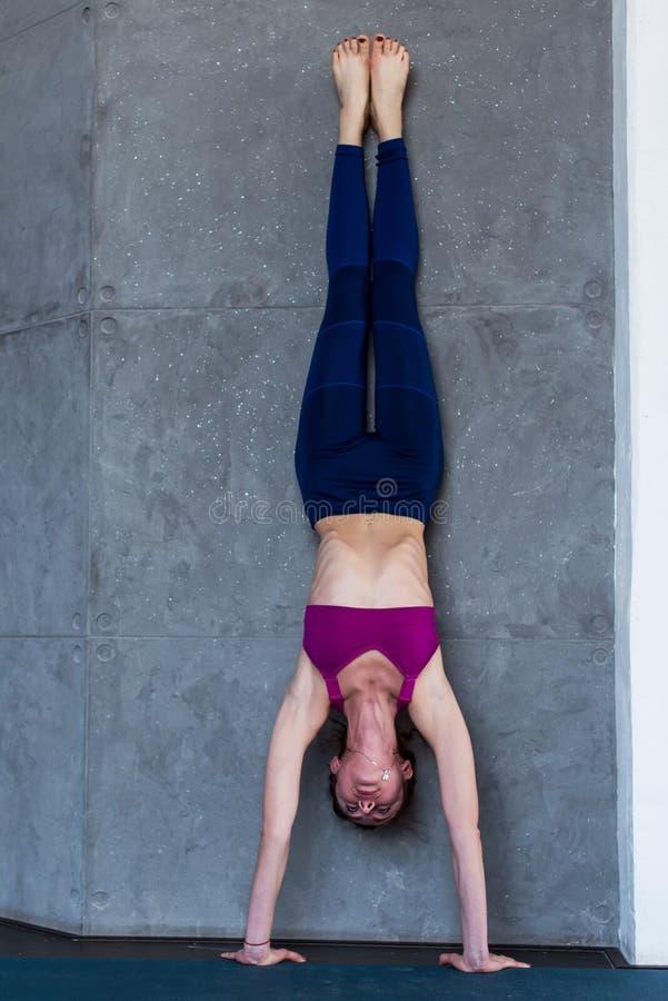 Chuderlawa bosa kobieta w sportswear robi handstand przeciw ścianie indoors obraz stock
