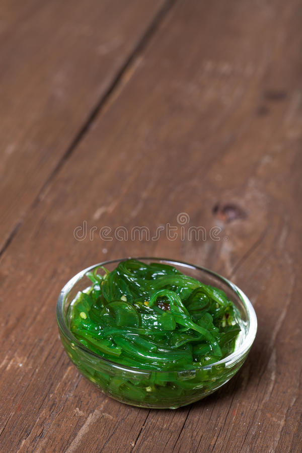 Chuka salad served in a small glass bowl on the old wooden table stock photo