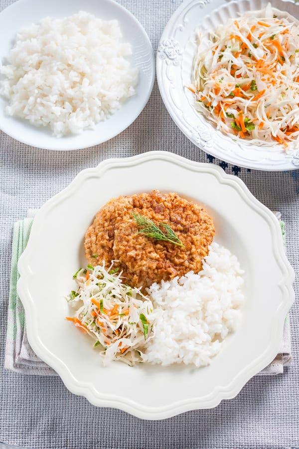 Chuleta de cerdo con arroz y ensalada de col imágenes de archivo libres de regalías